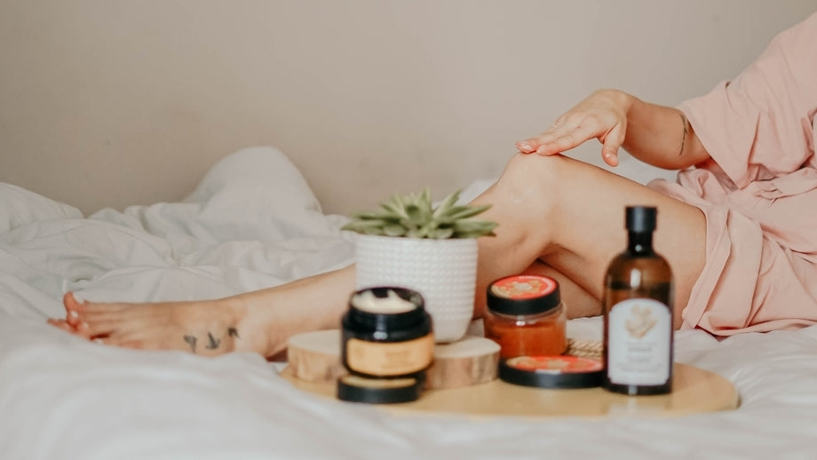 person in bed with an array of face and body creams