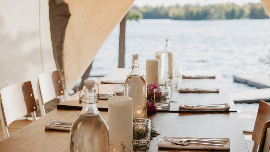 A rustic table set in a tent overlooking a lake