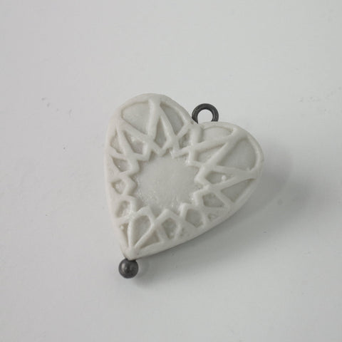 Small porcelain heart with star pattern and silver eye.