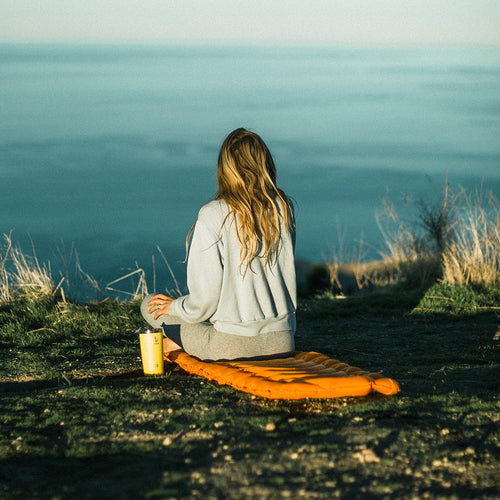 Women sitting on her Insulated Static V Lite on top of a hill looking out.