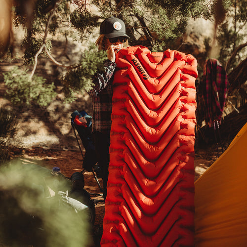 Women inflating the Insulated Static V outdoors next to trees and a tent