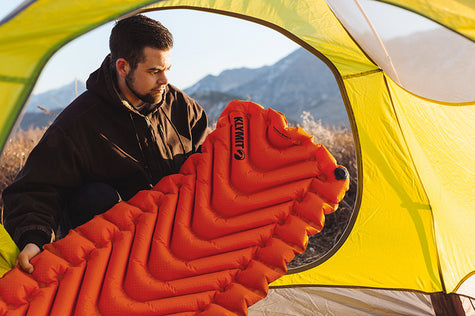 A man placing the inflated Insulated Static V into his tent.