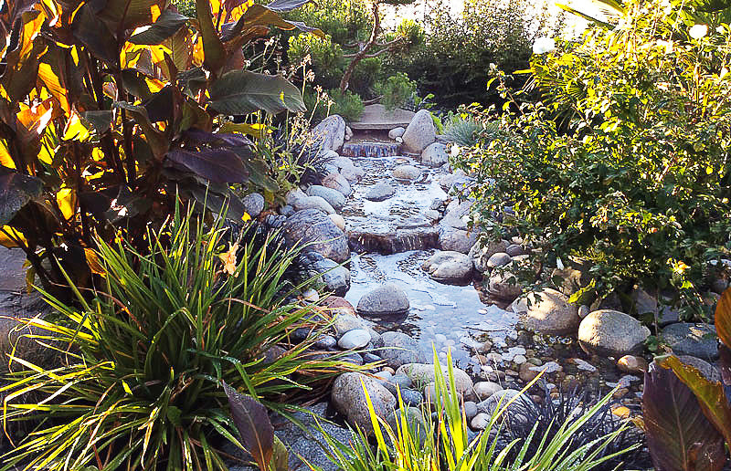 south surrey water feature with river by Scotty's Landscaping