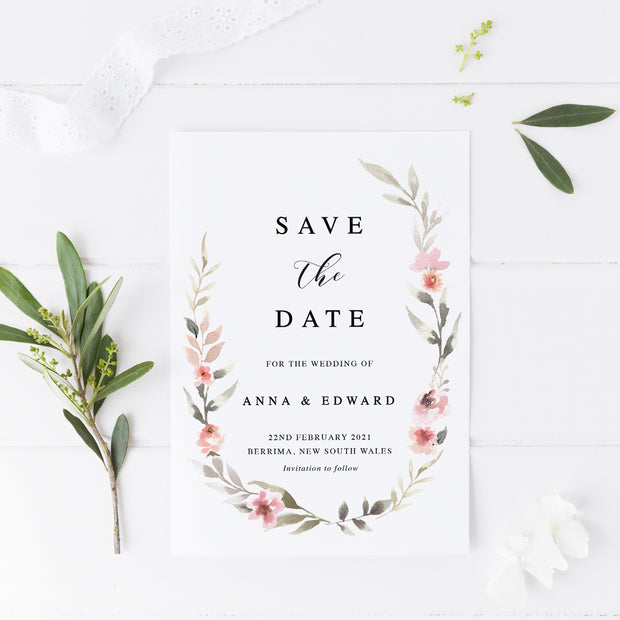 Wedding save the date card with soft pink floral wreath and calligraphy font in black