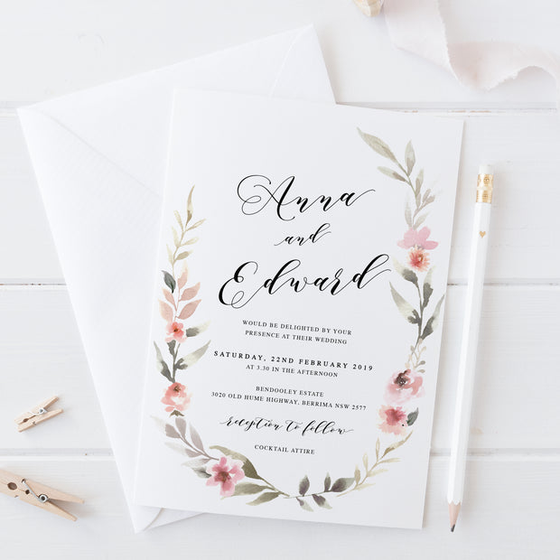 Wedding invitation with soft pink floral wreath and calligraphy font in black