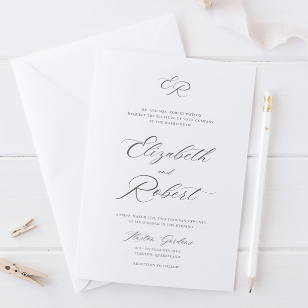 Elegant wedding invitation in grey and white with traditional calligraphy and monogram. Letterpress or foil printing.