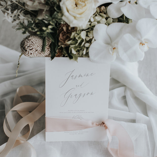 Botanical grey wedding invitation with hand drawn leaf and calligraphy, wrapped in blush silk ribbon