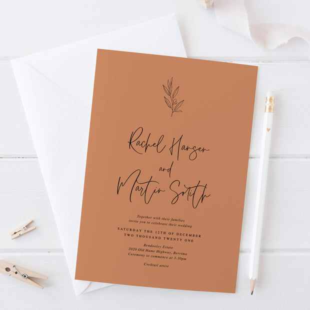 Wedding invitation on terracotta cardstock with hand drawn olive leaf element