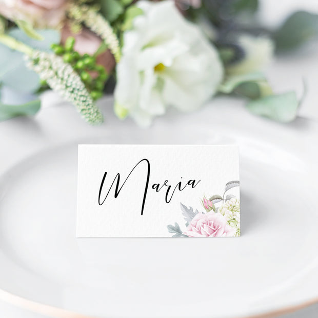 Folded wedding place card with calligraphy and pink flowers and greenery in corner