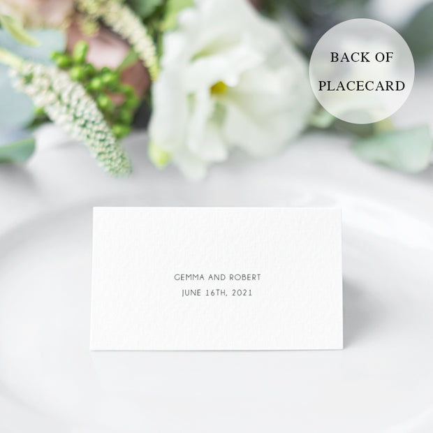 Folded wedding place card with calligraphy and pink flowers and greenery in both corners