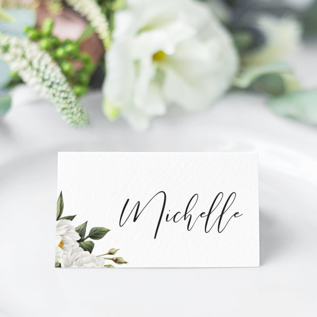 Folded wedding name cards or place cards with white flowers and green leaves and modern calligraphy font style