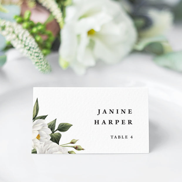 Folded wedding name cards or place cards with white flowers and green leaves and modern font style