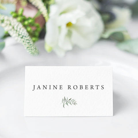 Wedding place card folded and featuring a soft green watercolour leaf and your guest names in natural charcoal.
