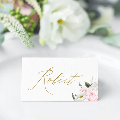 Wedding place cards with soft pink and apricot flowers and greenery, and beautiful calligraphy font in gold