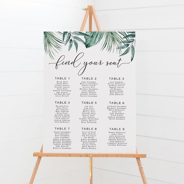 Wedding seating chart on board with tropical green leaves top border