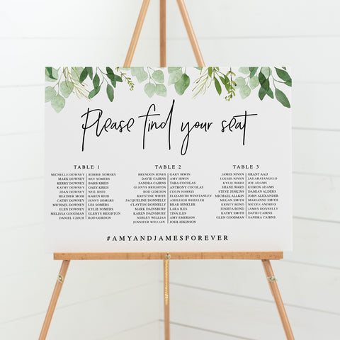Wedding seating chart on board with greenery leaf border
