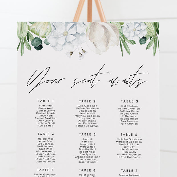 Wedding seating board with handwritten font and white flowers, green leaves