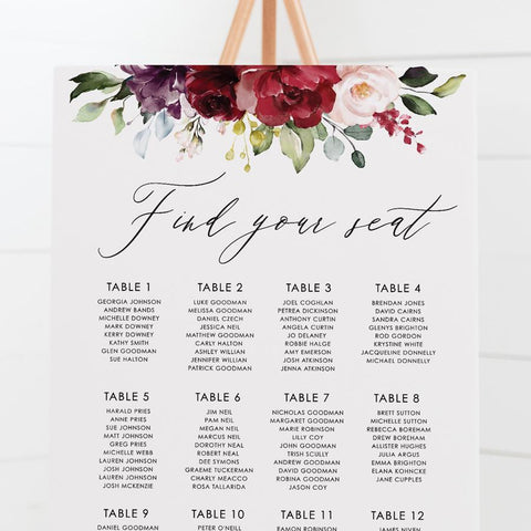 Wedding seating chart with striking red, burgundy and pink florals and foliage