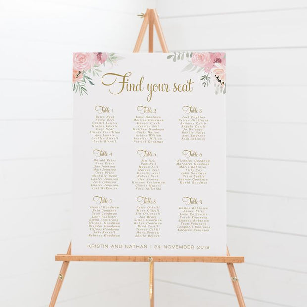 Wedding seating chart with gold text and soft pink flowers and leaves