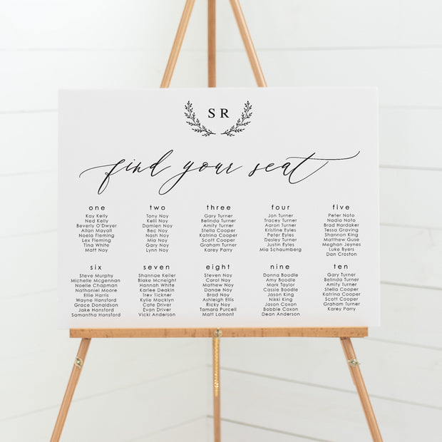 Wedding seating chart with monogram of initials and hand drawn wreath. Calligraphy font.