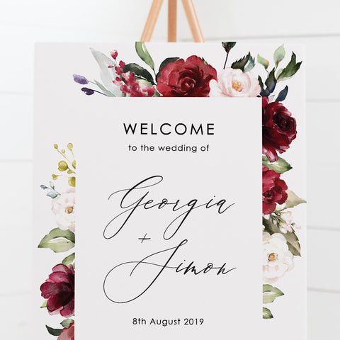 Wedding welcome sign with a border of deep red flowers and green foliage and beautiful calligraphy font, printed on card or foamboard