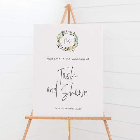 Wedding welcome sign board with watercolour wreath and monogram in neutral colour tones, bohemian style.