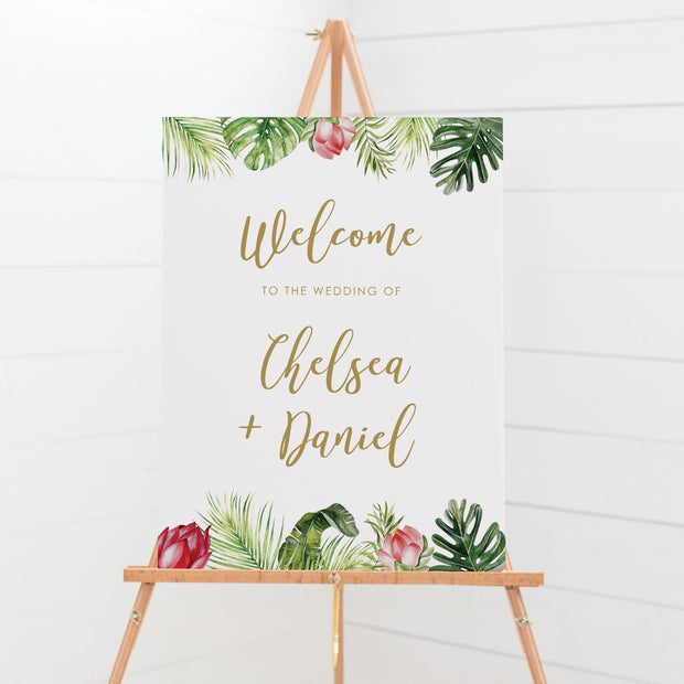Wedding welcome sign board with tropical florals top and bottom and gold text