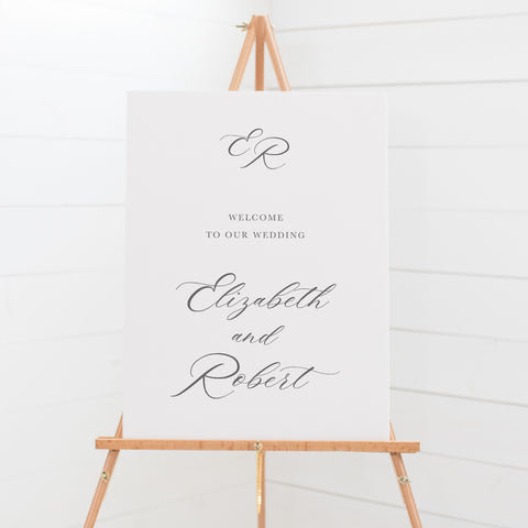 Traditional wedding welcome sign on board with calligraphy for the bride and grooms name and monogram at top.