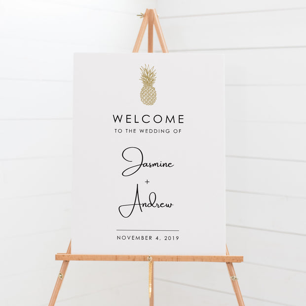 Wedding welcome sign with hand drawn tropical pineapple in gold and modern script font for bride and grooms names