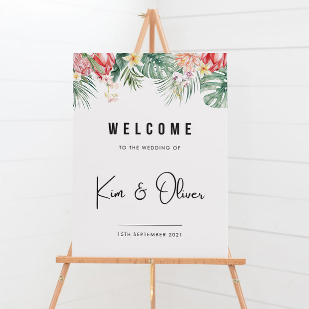 Wedding welcome sign board, tropical leaves and flowers as top border