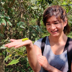 Founder, Lily at the peace silk farm with silkworm in palm of hand, India