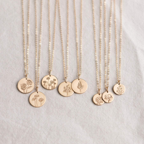 gold birth flower necklaces on sheet