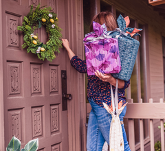 woman knocking on door with reusable gift bags