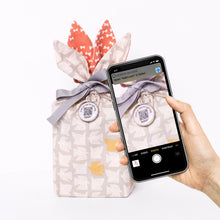 Load image into Gallery viewer, Scanning the Tokki gift tag to see or create the Tokki digital gift card