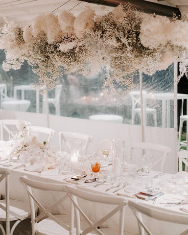 Neutral, white, minimalist wedding table with white chairs and a dried floral cloud-shaped installation with baby's breath and white flowers