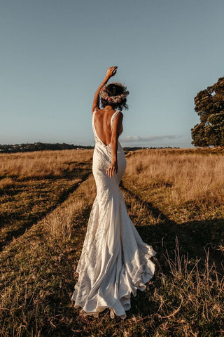 Bohemian, mermaid cut wedding dress with a flower crown made of fresh and dried florals in a field of hay