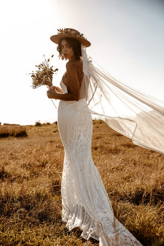 Bohemian, mermaid cut white wedding dress with a small, minimalist dried floral bouquet and a dried floral hat