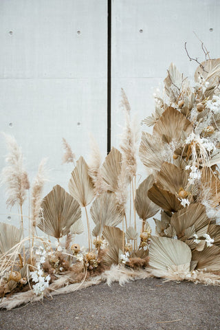 Dried floral wedding installation with palm spears and dried pampas grass