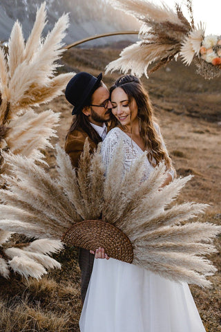 Wedding photo of couple holding dried pampas suns with bohemian inspired wedding dress and accessories; bohemian inspired wedding photography