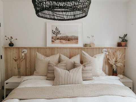 Bed with a wooden slate headboard and beautiful neutral-toned patterned cushions for a minimalist and boho-chic home decor inspiration