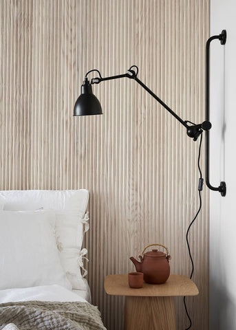 Wood slate headboard with a black minimalist lamp and white accents