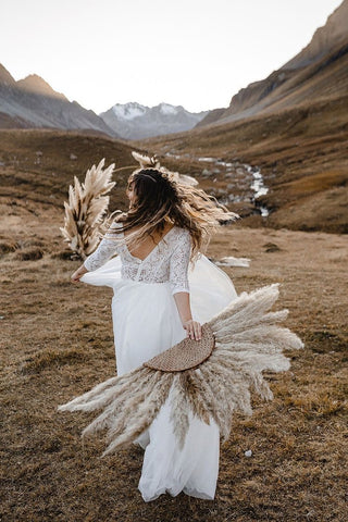 Wedding photo of bride holding dried pampas suns and a dried pampas bouquet with bohemian inspired wedding dress and accessories; bohemian inspired wedding photography