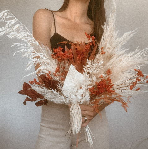 Bridal/wedding bouquet using pampas grass, dried palms, and other dried florals to make a white and neutral toned bouquet with small red and orange accents for bohemian-inspired weddings