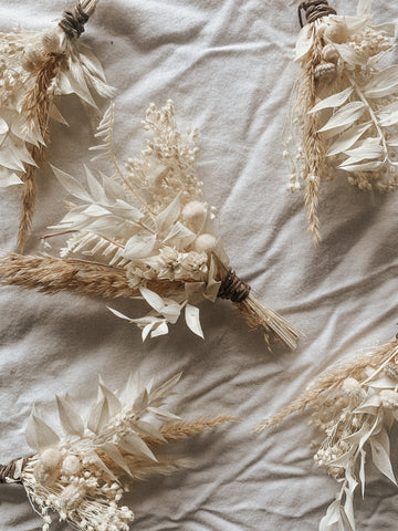 Dried floral boutonnieres using baby's breath, dried pampas grass and other white dried florals