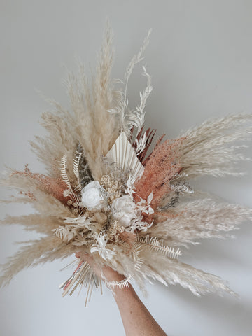 Beautiful dried floral bridal bouquet with pampas grass, dried palm spears, roses, and other dried florals using white and neutral tones with a touch of pink