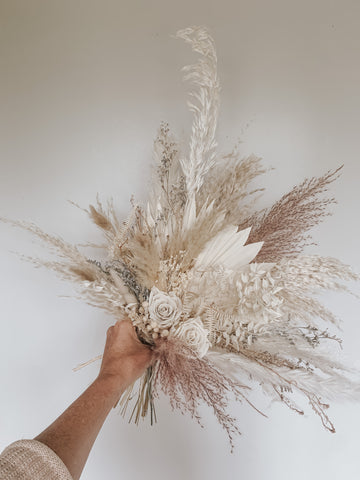 Dried floral wedding and bridal bouquet using pampas grass, dried palms, and white roses for a minimalist, boho-chic, or California desert inspired bridal look/wedding decor