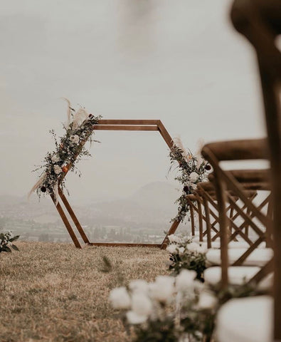 Dried floral, eucalyptus, and pampas grass wedding venue install surrounding a wedding arch; boho inspired wedding trends, perfect for summer weddings
