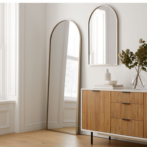 Arched mirrors from West Elm in a minimalist style bedroom with a natural wood chest of drawers