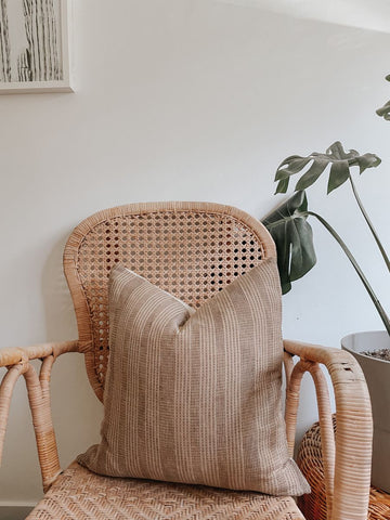 Neutral toned cushion with simple pattern on an earth-toned wicker chair for minimalist and boho-chic home decor inspiration