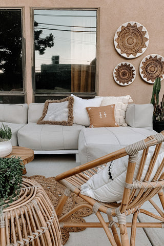 Neutral toned outdoor patio with a grey couch, outdoor cushions and pillows, rattan furniture and wicker baskets inspired by boho-chic and minimalist home decor